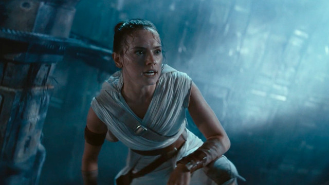 rey climbs up a piece of the fallen death star and takes a deep breath