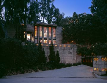 The Storer House by Frank Lloyd Wright. The facade is grey brick and there are multiple tall windows on the front of the house. The house is surrounded by shrubbery and trees.