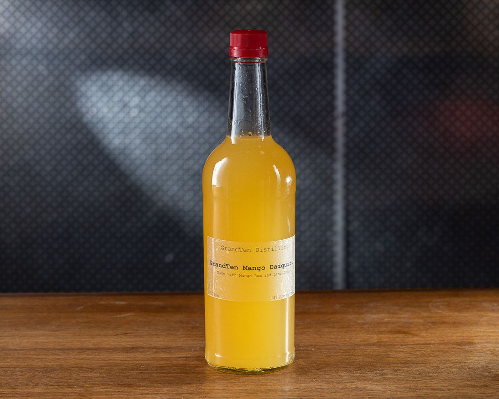 Isolated photo of a bottle of an orange cocktail on a wooden counter