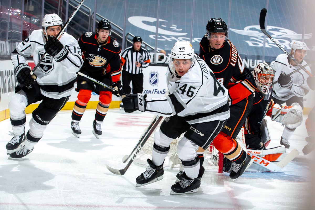 Trevor Moore #12 and Blake Lizotte #46 of the Los Angeles Kings and Ben Hutton #7, Isac Lundestrom #48 and goaltender John Gibson #36 of the Anaheim Ducks look on during the first period of the game at Honda Center on March 8, 2021 in Anaheim, California.
