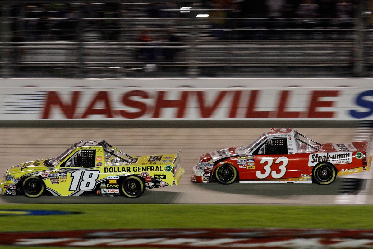 Kyle Busch, driver of the #18 Dollar General Toyota, leads Ron Hornaday Jr., driver of the #33 Steak Umm Chevrolet, during the NASCAR Camping World Truck Series Bully Hill Vineyards 200 at Nashville Superspeedway on April 22, 2011 in Lebanon, Tennessee.