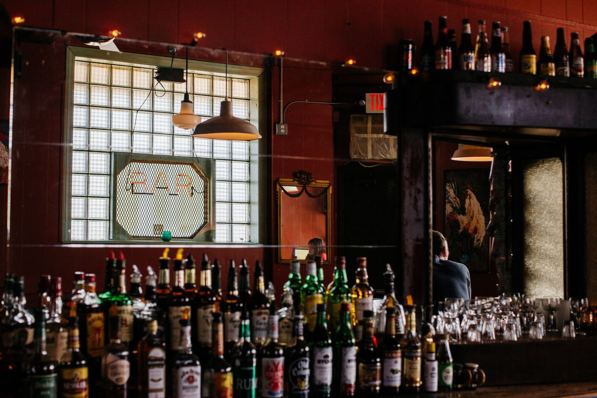 """The back bar at Bumbo's has a neon """"Bar"""" sign hanging in the window and bottles of liquor lined up on the counter."""