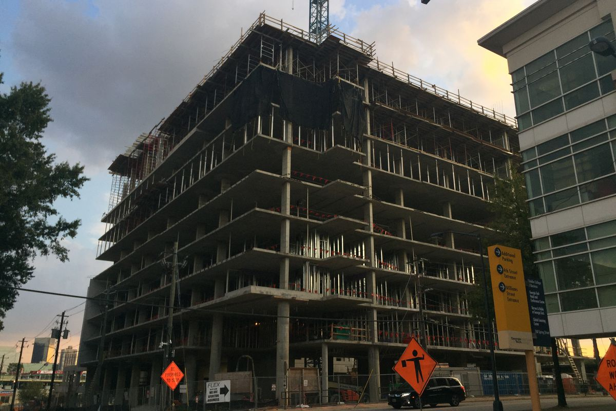A concrete frame, rising 10 stories above the street.