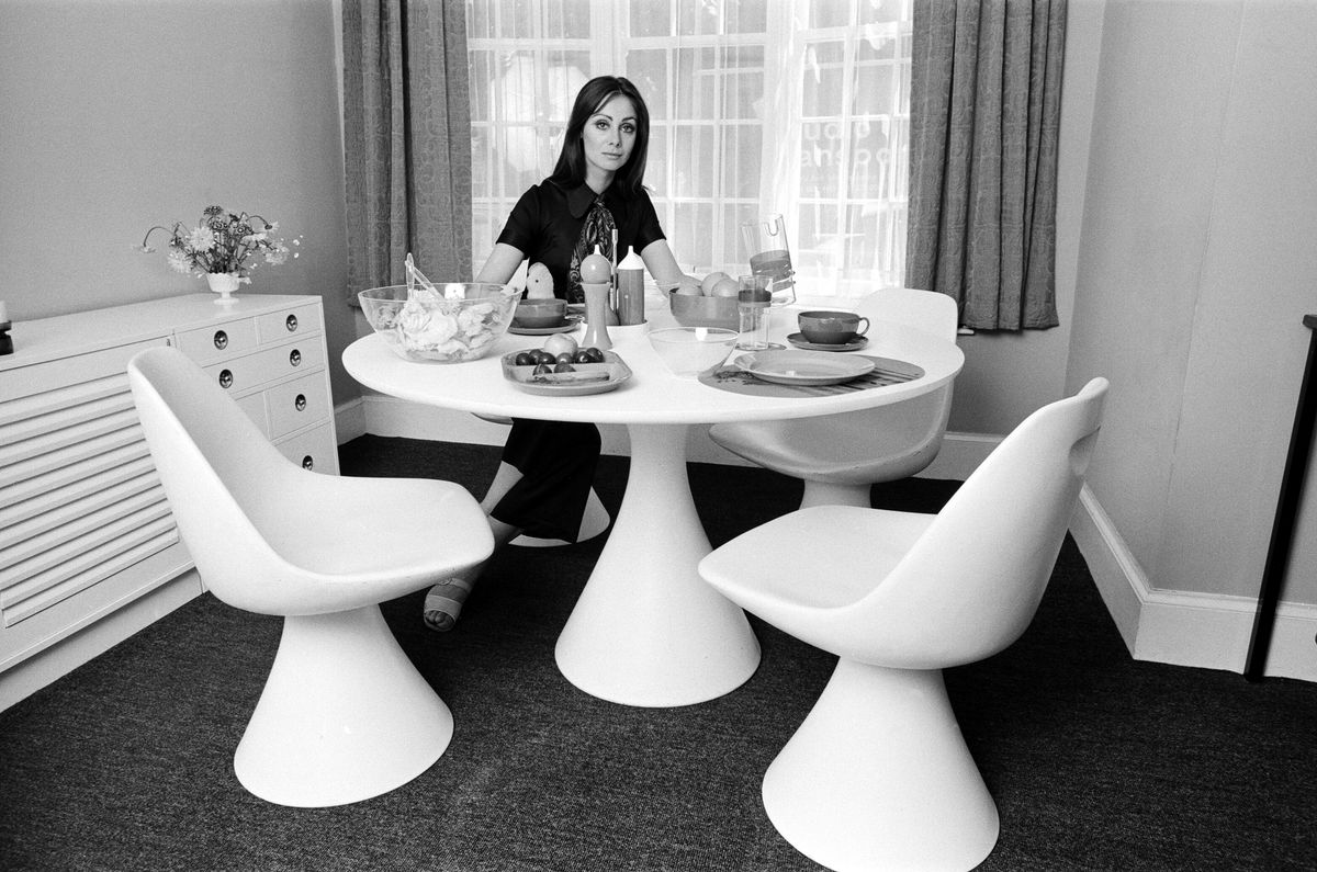 A 1969 photograph of a woman sitting in a modern dining space.