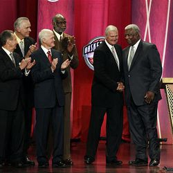 Basketball Hall of Fame inductees, members of the 1960 U.S. Olympics team, applaud as Jerry West, second from right, and Oscar Robertson shake hands during enshrinement ceremonies in Springfield, Mass., Friday.