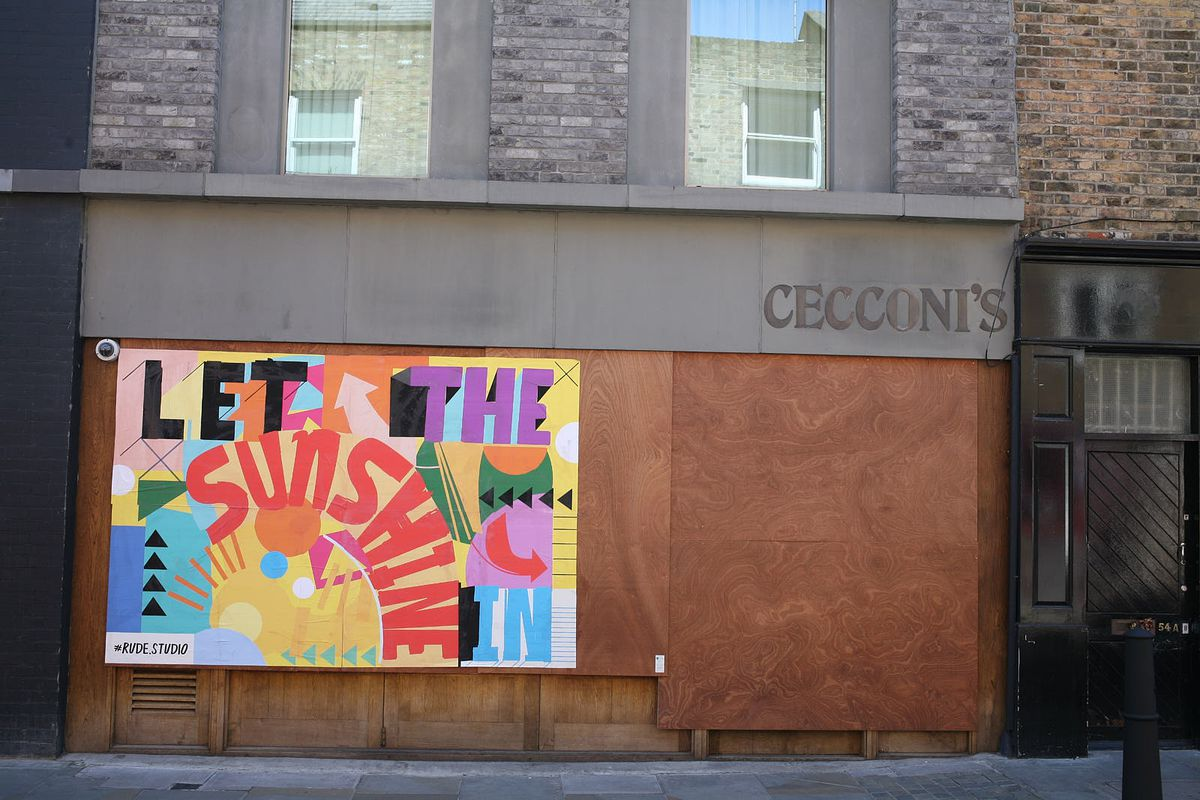 """A restaurant is boarded up and covered in optimistic graffiti that says """"let the sun shine"""" on Redchurch Street in Shoreditch"""
