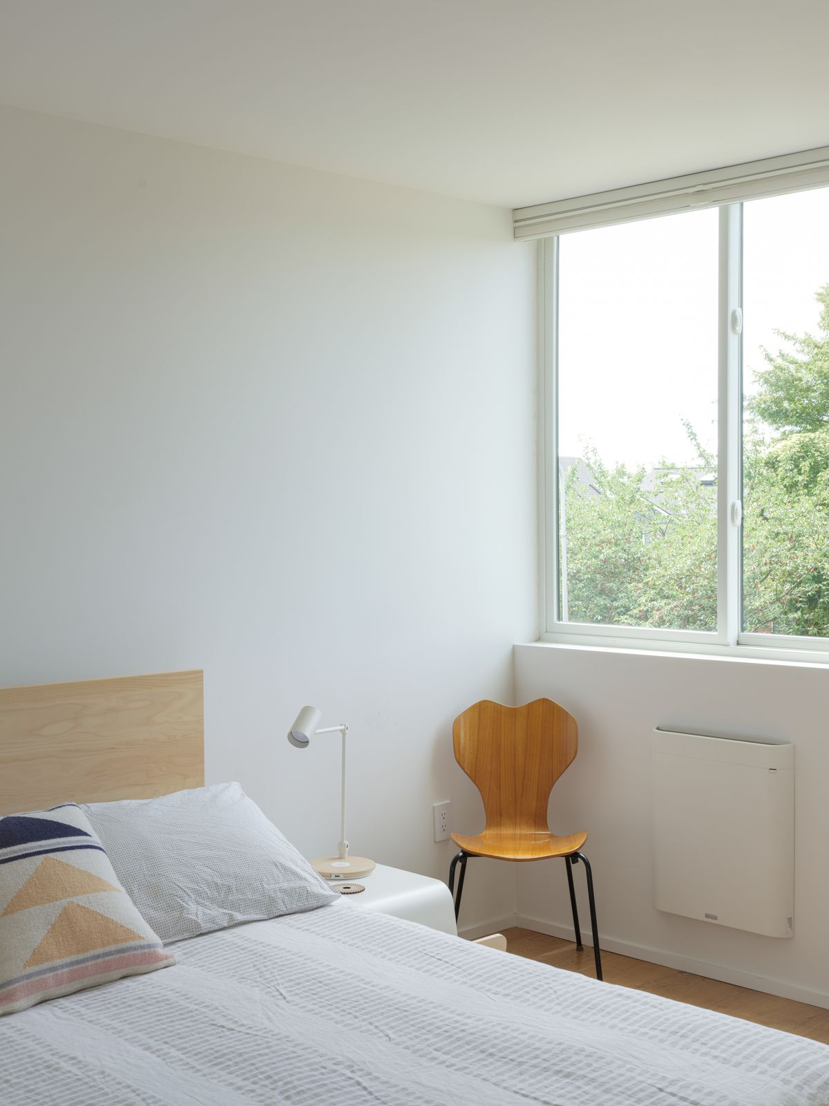 A bedroom with a bed that has patterned white bed linens and multiple pillows. There is a wooden chair. A window has a view overlooking trees.