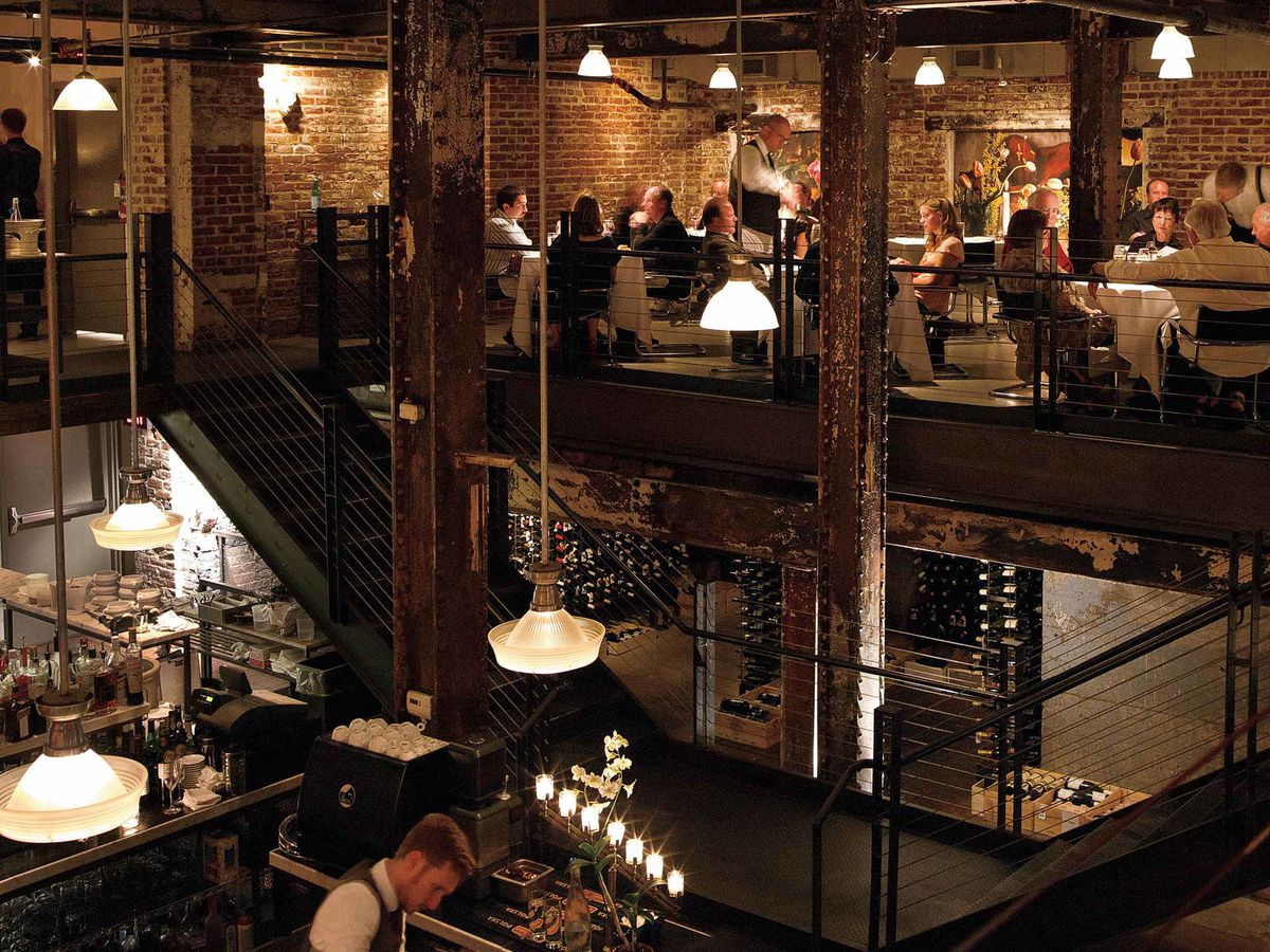 A red brick, two-level interior with large steel beams, metal stairs and railings, tables beneath pendant lights, and open kitchen on the main floor