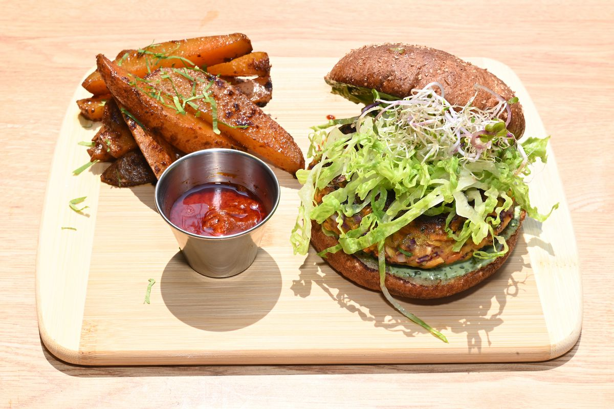 A bright shot of a veggie burger on a wooden platter with fries on the side.