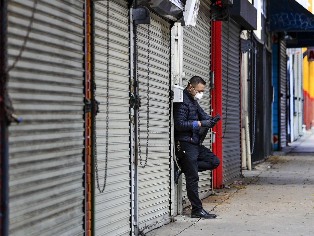 A masked man in a light black coat leans against a wall on a block full of closed metal shop gates.