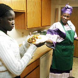 Sudanese refugee Alual Majok, right, hands a dish of rice and kabob to her daughter Atul, 12, at their apartment in Taylorsville recently.