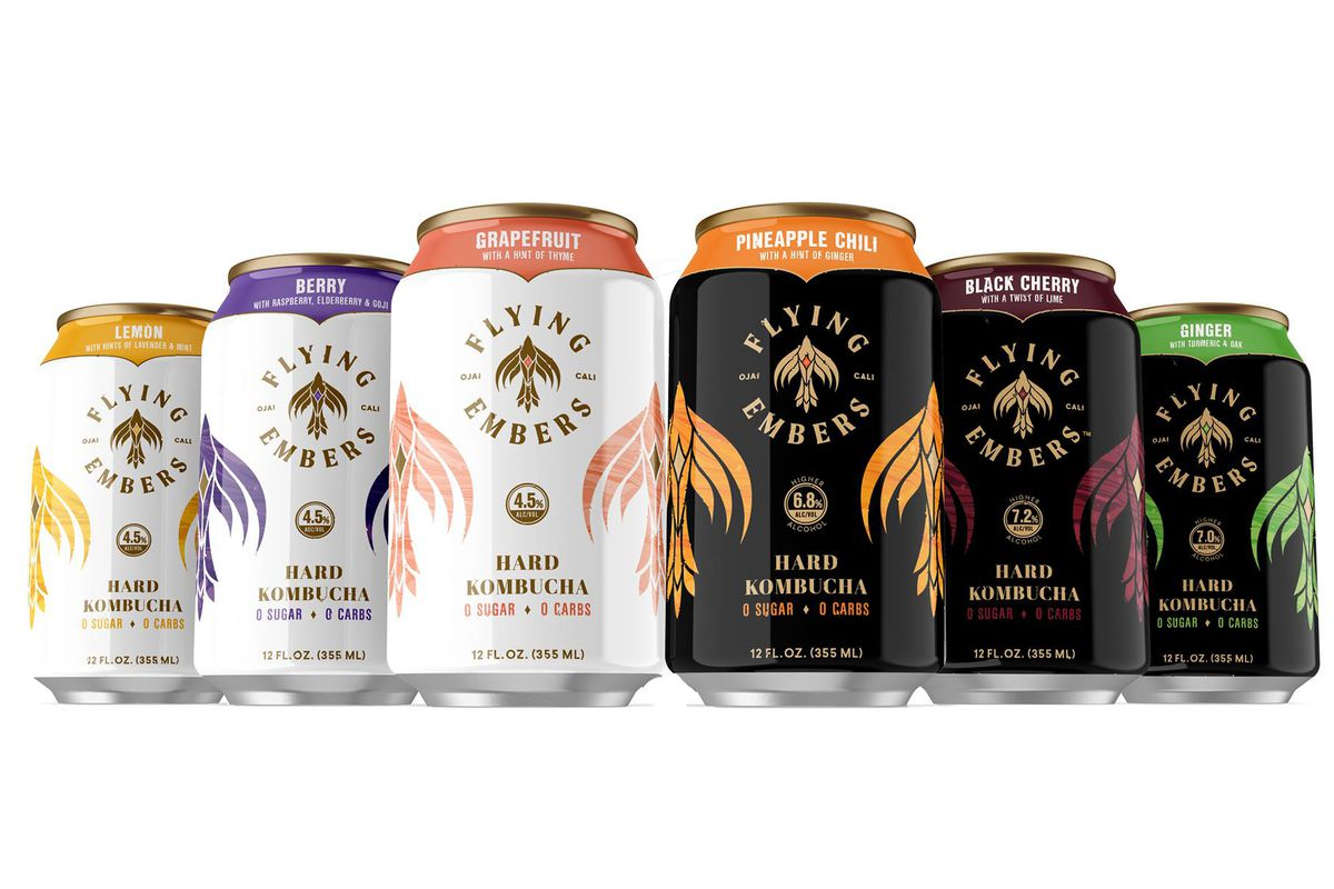 A lineup of six hard kombucha cans from the brand Flying Embers on a white background. The three cans on the left are white; the three on the right are black.