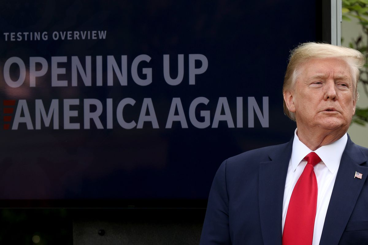 """President Trump during the coronavirus news conference with a sign behind him that reads """"Opening up America again."""""""