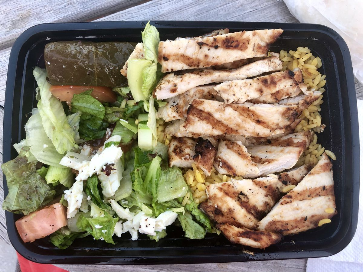 Grilled chicken atop yellow rice alongside salad with stuffed grape leaves