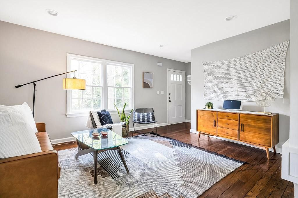 A living room with old wood floors and gray walls.