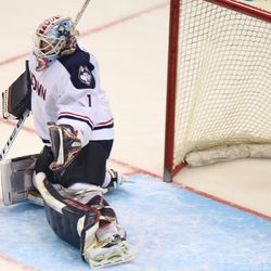 The puck goes past UConn's Tanner Creel into the corner boards.