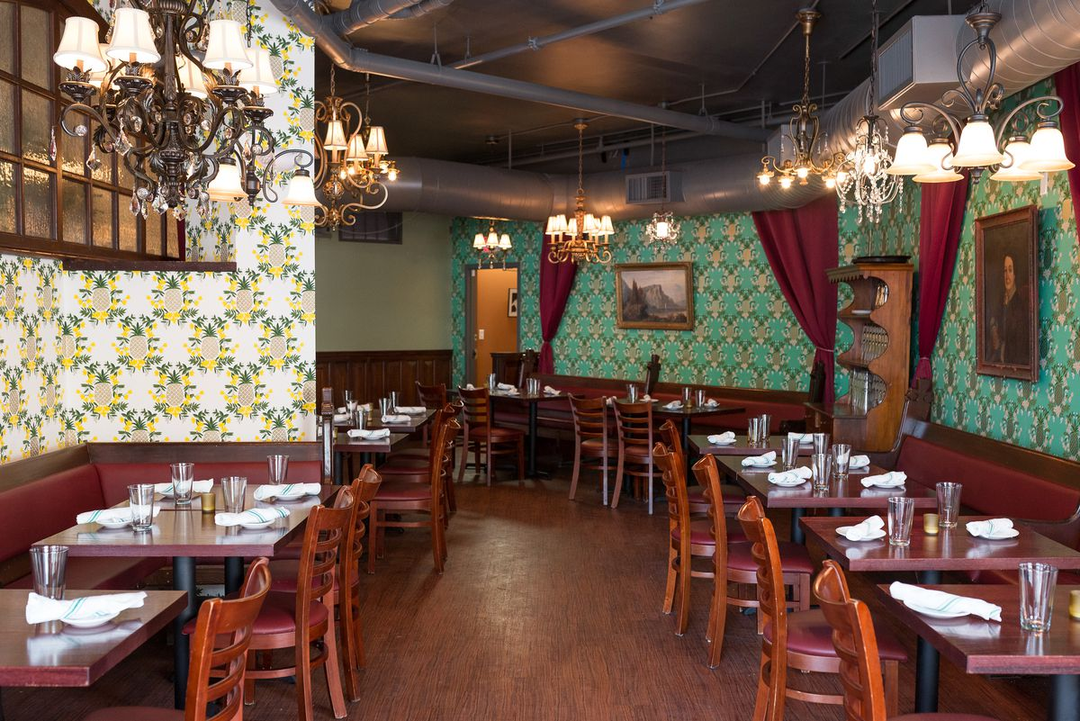 A restaurant interior features two different eye-catching wallpapers; one is white with a yellow and green pineapple pattern, and the other has teal and gold diamonds. Red velvet curtains hang in several places.