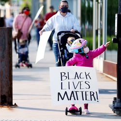 Scarlett Herrern reaches for the crosswalk button as she and her family join several hundred demonstrators who gathered to march for Black Lives Matter at Daybreak in South Jordan on Wednesday, June 17, 2020.