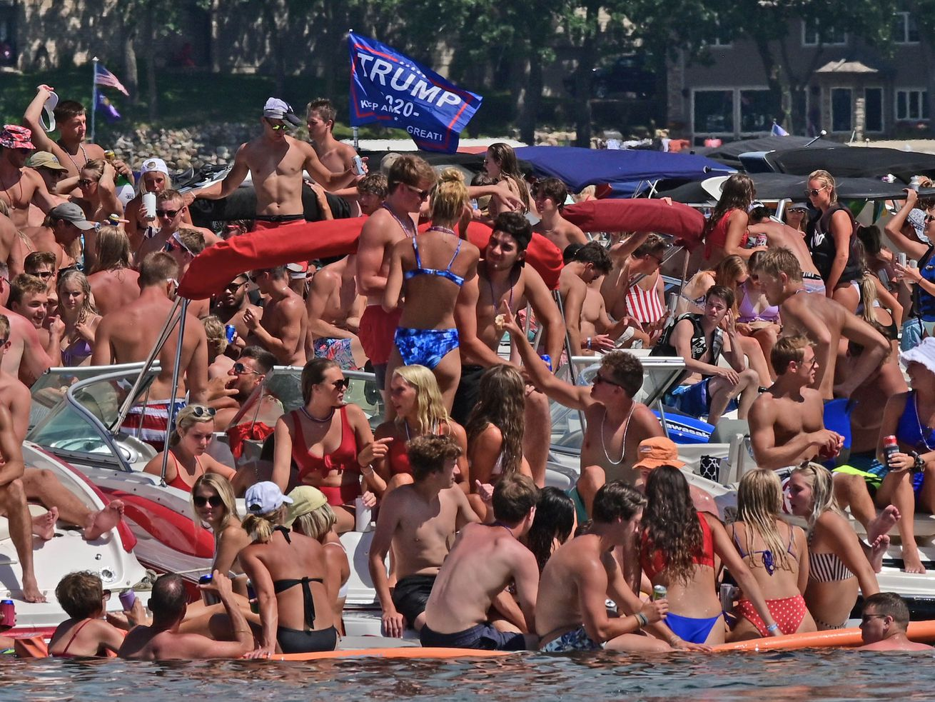 A crowd of people in bathing suits floating on rafts on a lake.