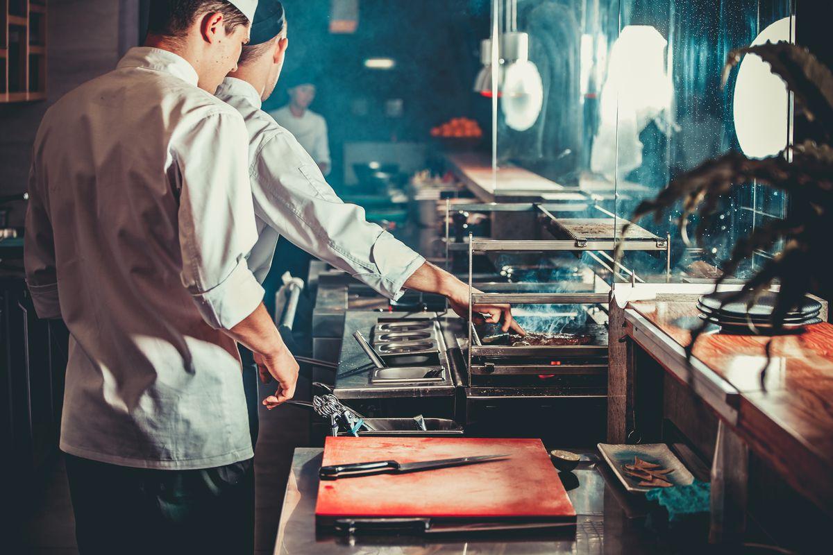 Three cooks in a restaurant kitchen