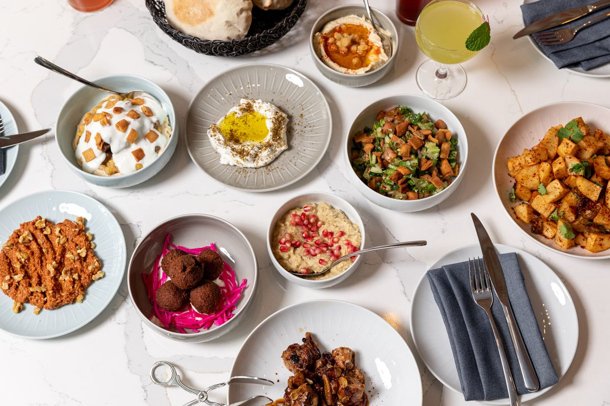 A white marble table filled with different mezze plates.