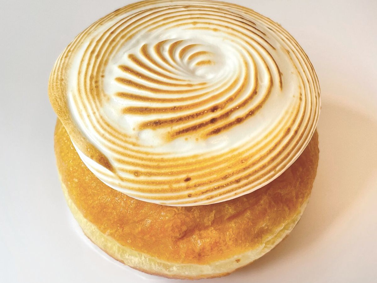 A plain doughnut has a swirled topping of toasted white meringue.