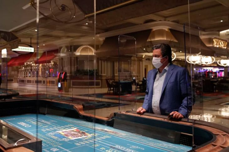 Bill Hornbuckle, acting CEO and president of MGM Resorts International, stands between acrylic barriers used as a coronavirus safety precaution at a craps table in the Bellagio Hotel and Casino in Las Vegas.