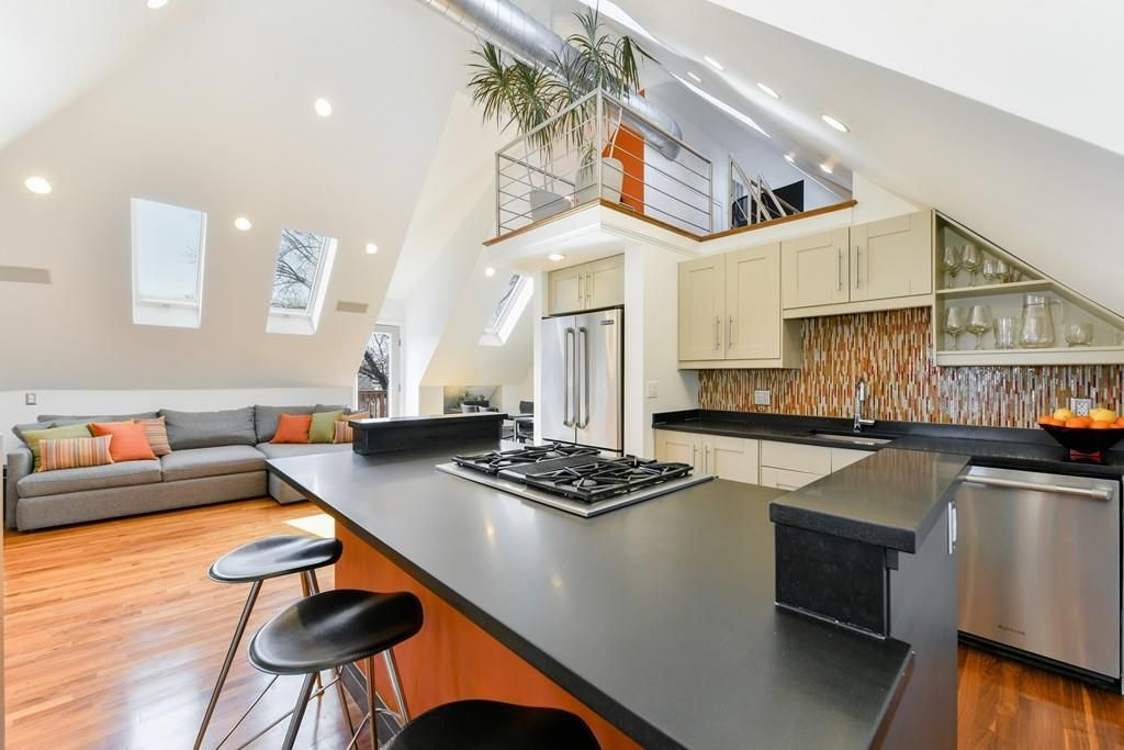 A capacious open living room-kitchen with a loft with a balcony overlooking it.