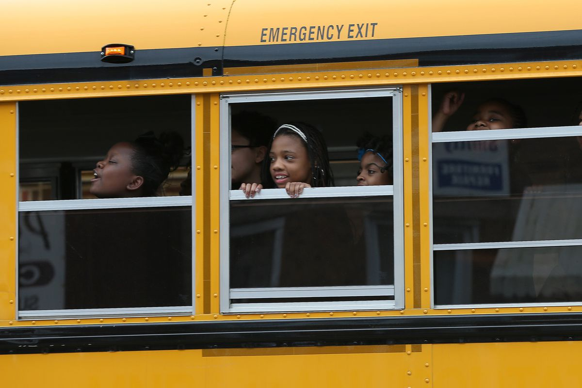 A girl looks out the window of a school bus