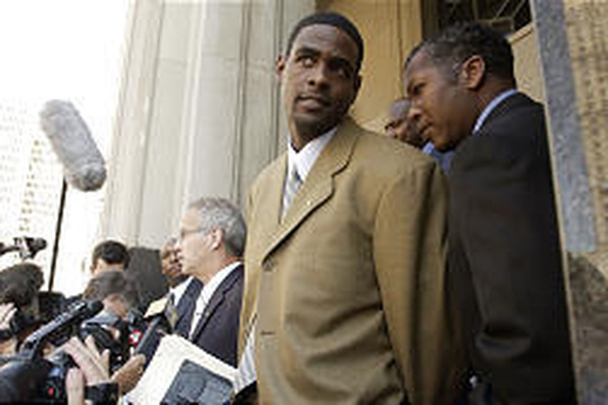 Sacramento Kings' Chris Webber waits while his lawyer talks to reporters outside federal court Tuesday.