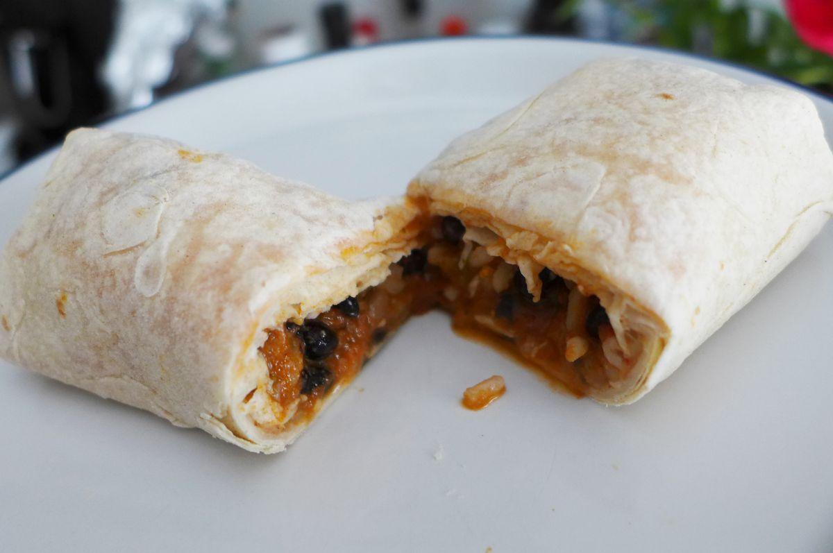 A tiny burrito cut in half to reveal the interior.