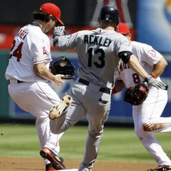 Seattle Mariners' Dustin Ackley is out at first after grounding to Los Angeles Angels first baseman Kendrys Morales, right, who tossed to pitcher Dan Haren in the first inning of a baseball game in Anaheim, Calif., Thursday, Sept. 27, 2012.