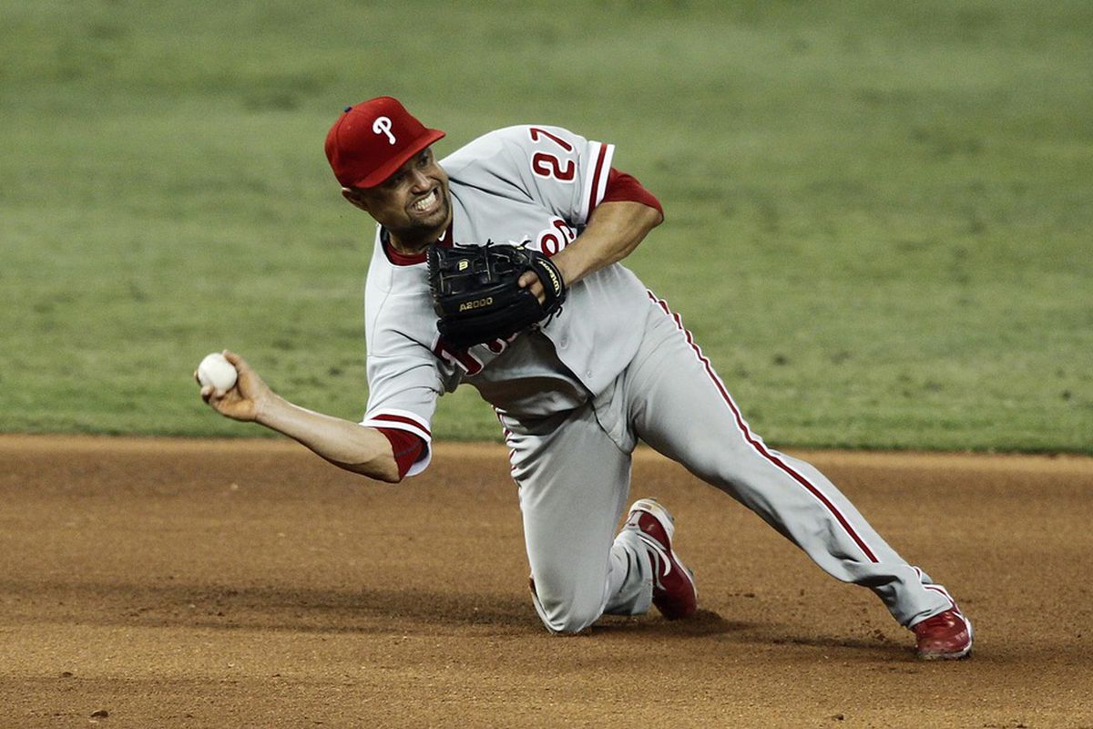 June 30, 2012; Miami, FL, USA;  Philadelphia Phillies third baseman Placido Polanco (27) throws out Miami Marlins player Omar Infante (not pictured) in the eighth inning at Marlins Park. Mandatory Credit: Robert Mayer-US PRESSWIRE