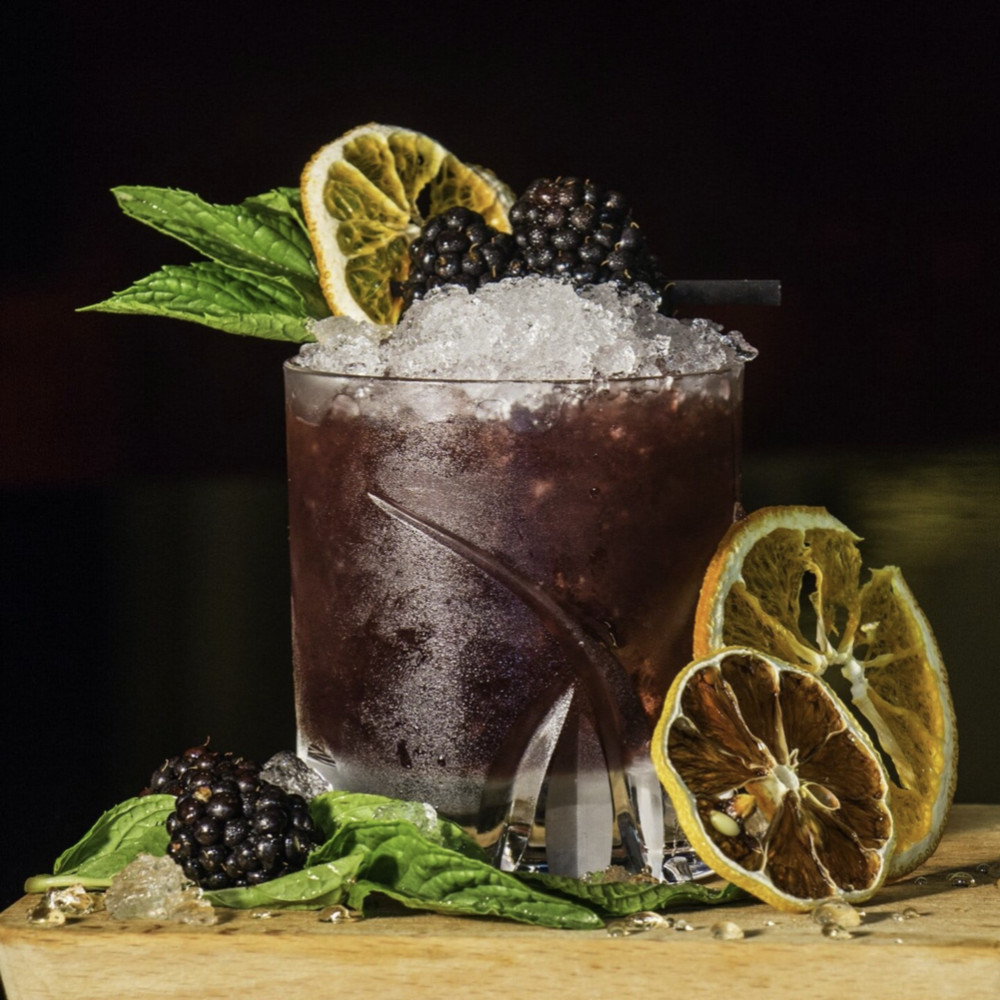 A dark purple cocktail in a tumbler, dressed with blackberries, preserved lemons, and various fresh herbs