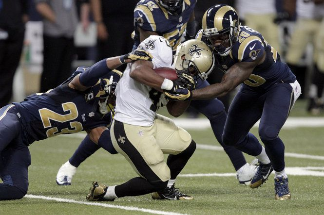 New Orleans Saints running back Darren Sproles, center, is pulled down by St. Louis Rams safety Rodney McLeod, left, and safety Darian Stewart during the fourth quarter of an NFL football game Sunday, Dec. 15, 2013, in St. Louis. (AP Photo/Tom Gannam)