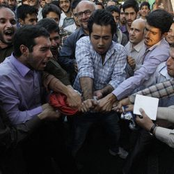 Iranian protesters tear up a French flag in front of the French Embassy during a demonstration to condemn a French magazine caricaturing prophet Muhammad in Tehran, Iran, Sunday, Sept. 23, 2012.