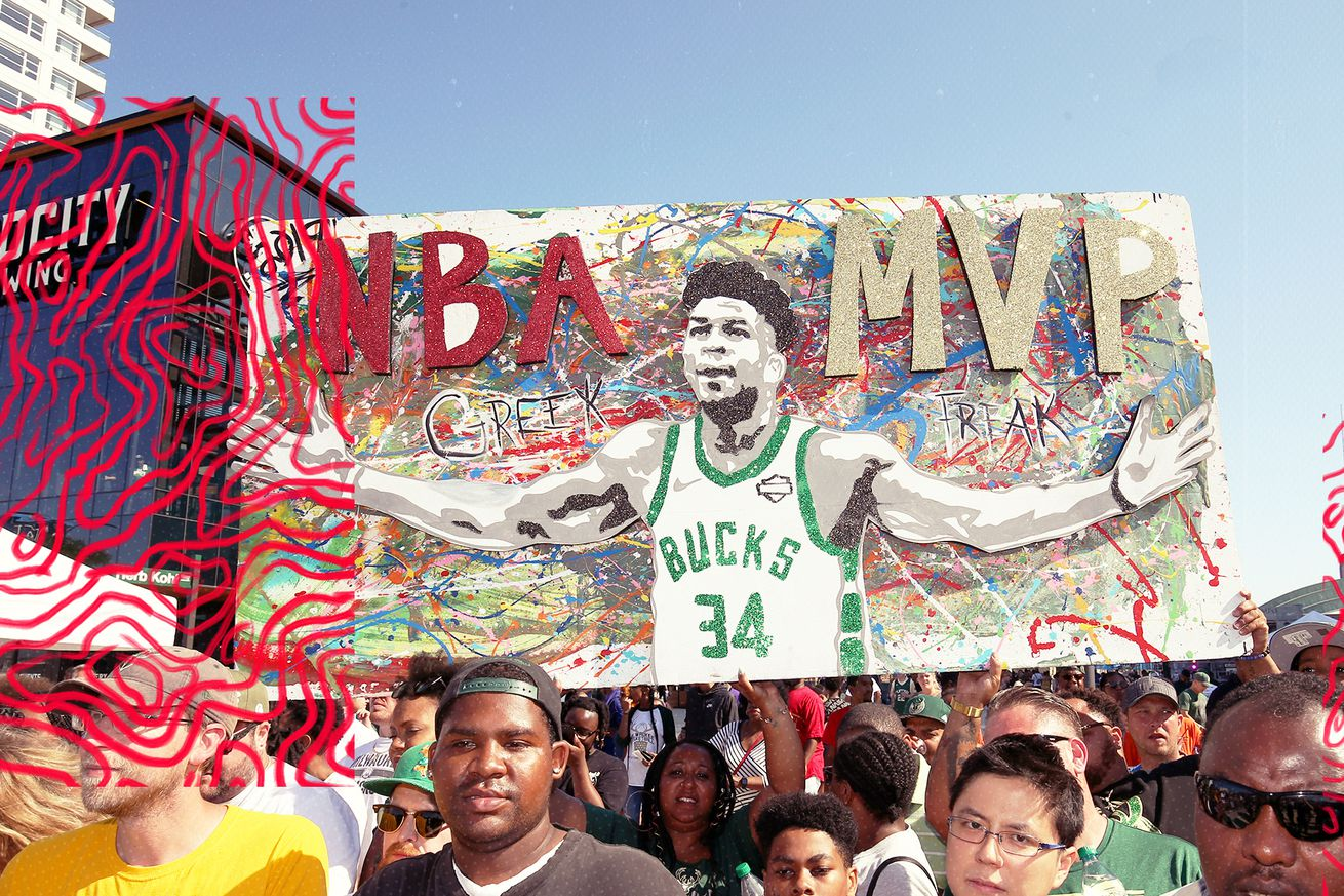 NBA fans hold a sign of Giannis Antetokounmpo while marching in the streets.