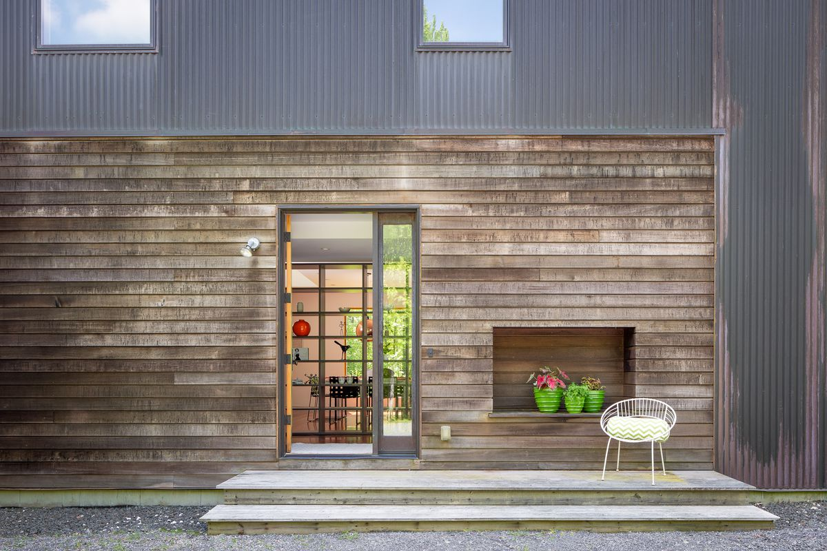 An exterior view of an entrance to a wood and copper house. There's three plants and a white modern chair in front on a patio.