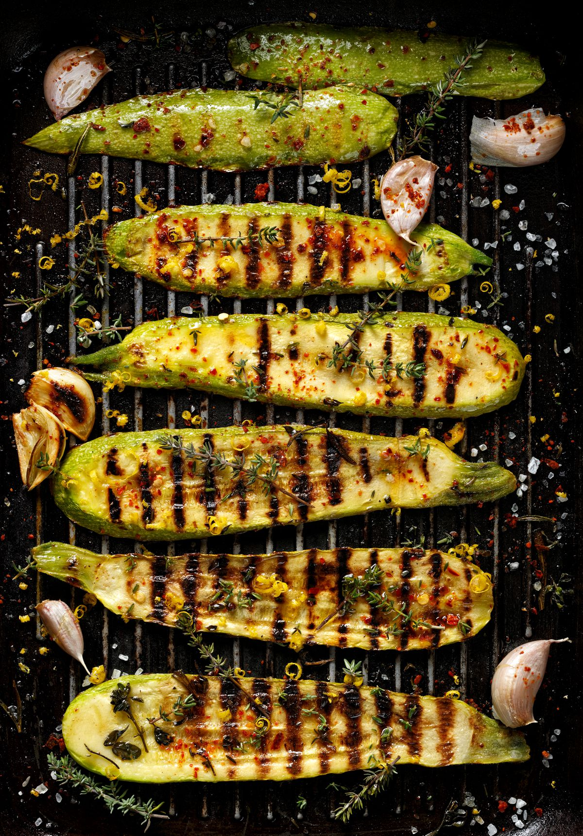 Halved zucchinis sit on a grill, with grill marks visible on the vegetables. A few cloves of garlic are scattered around them.
