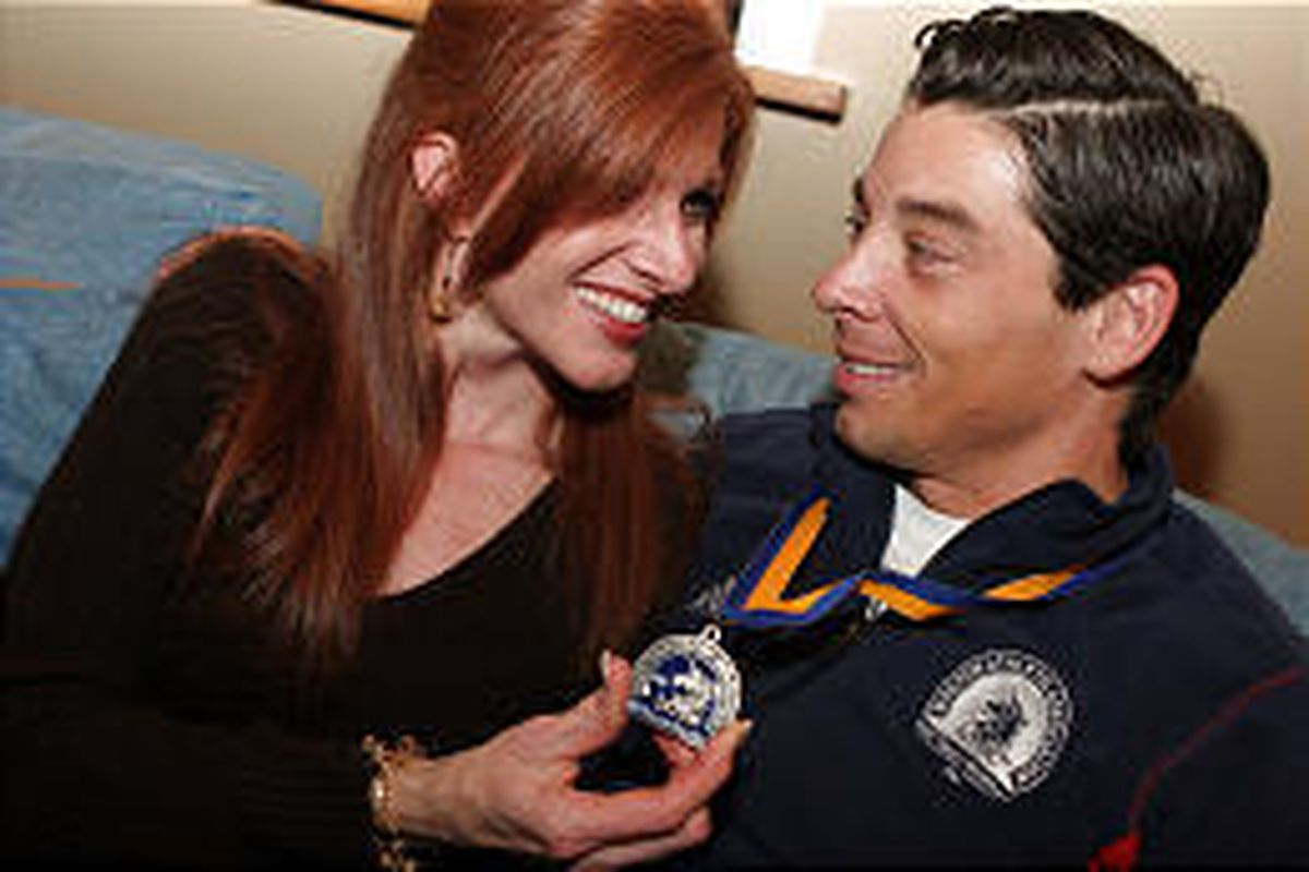 David Roskelley sits with his wife, Lynda, who holds a medal David received by competing in the 2006 Boston Marathon.