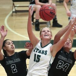 Olympus forward Alyssa Blanck grabs a rebound between Highland's Lei Makaui, left, and Sosefina Langi during a game at Olympus High School in Holladay on Tuesday, Jan. 5, 2021.