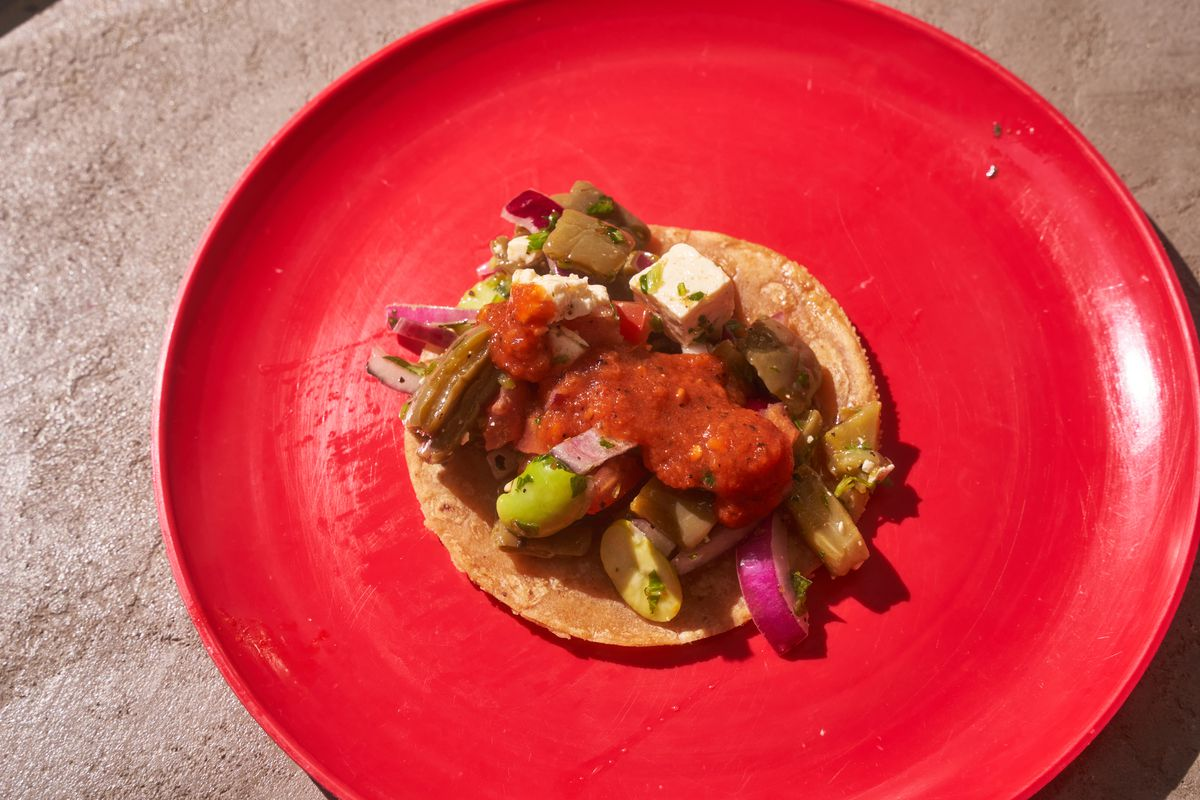 A taco filled with cactus, fava beans, cheese, and red onion sits on a small tortilla on a red plate