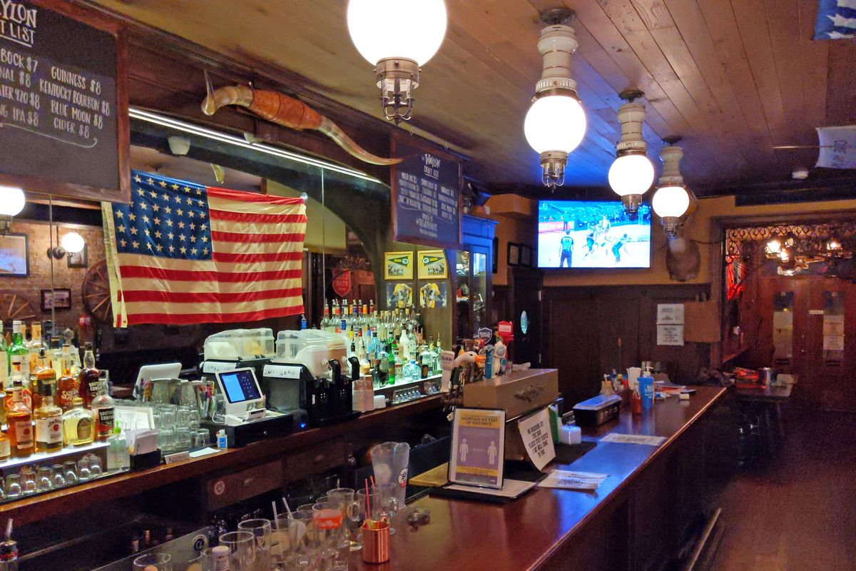 An antique bar, busy with kitsch, over which hangs and American flag.