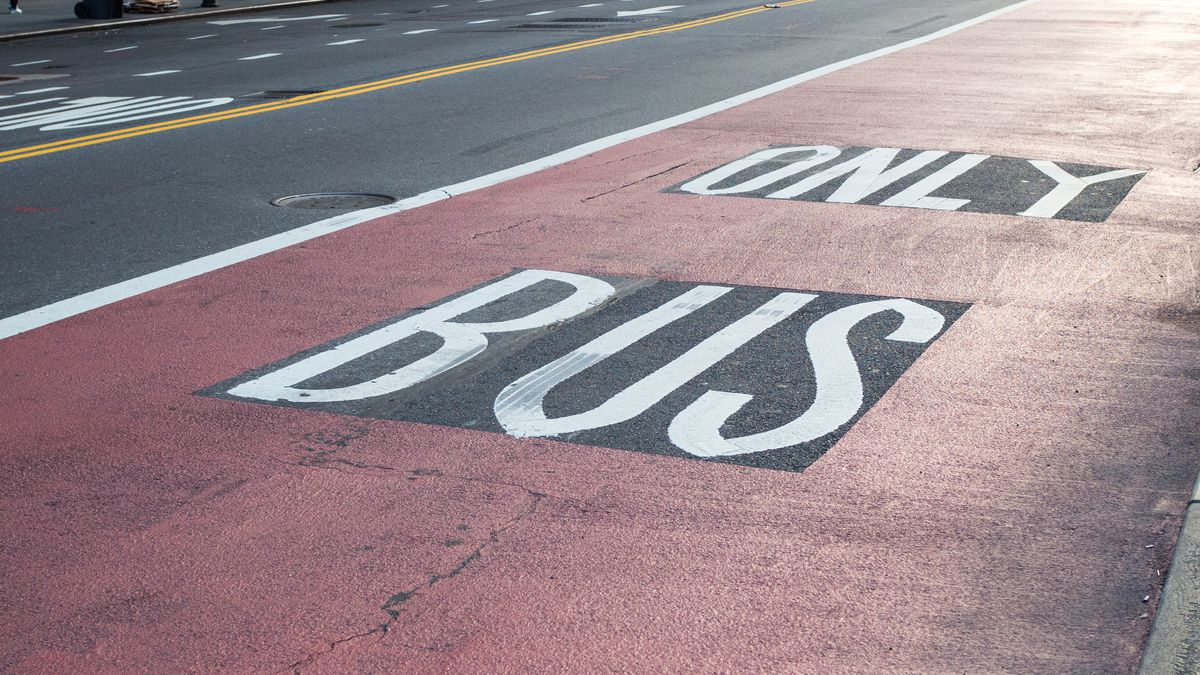 A asphalt bus lane in New York City painted with red paint.