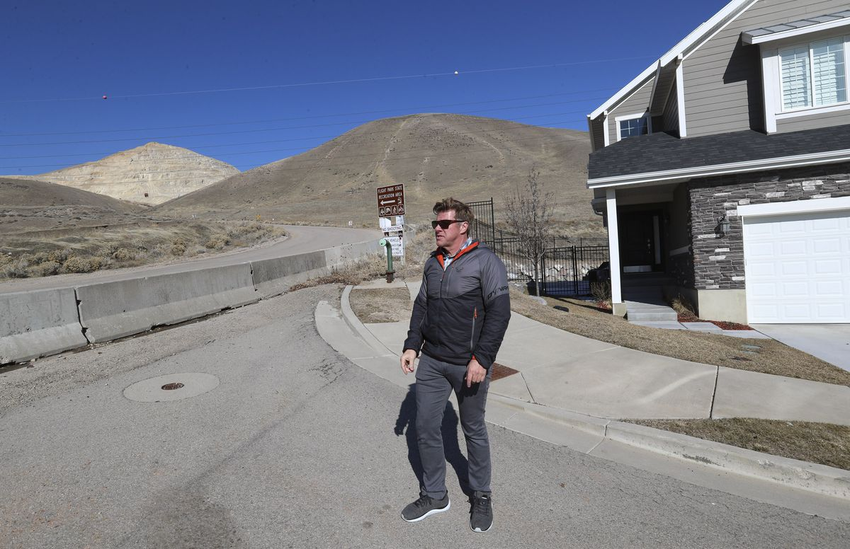 A huge rock cliff, left, created byGeneva Rock's gravel operations looms in the background as Delane Barrus talks about the gravel project from the end of the subdivision where he lives in Lehi on Friday, Feb. 21, 2020.
