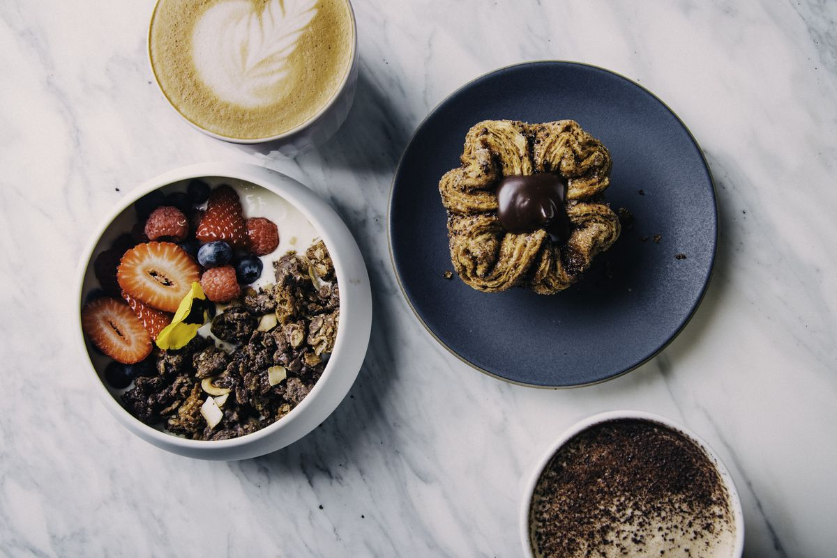 An assortment of breakfast items at Bloom, including granola and a chocolate kouign amann