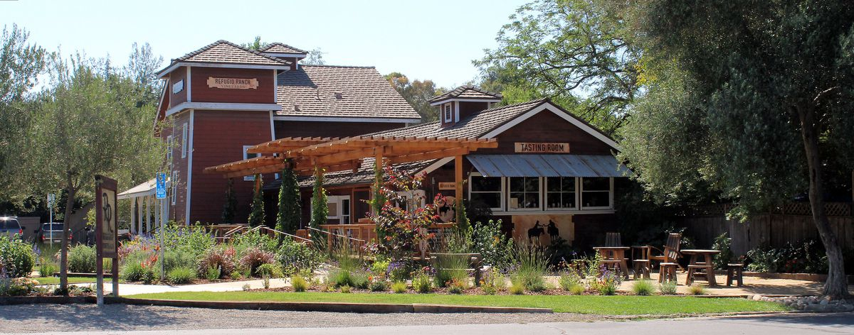 A red farmhouse tasting room winery space surrounded by trees.