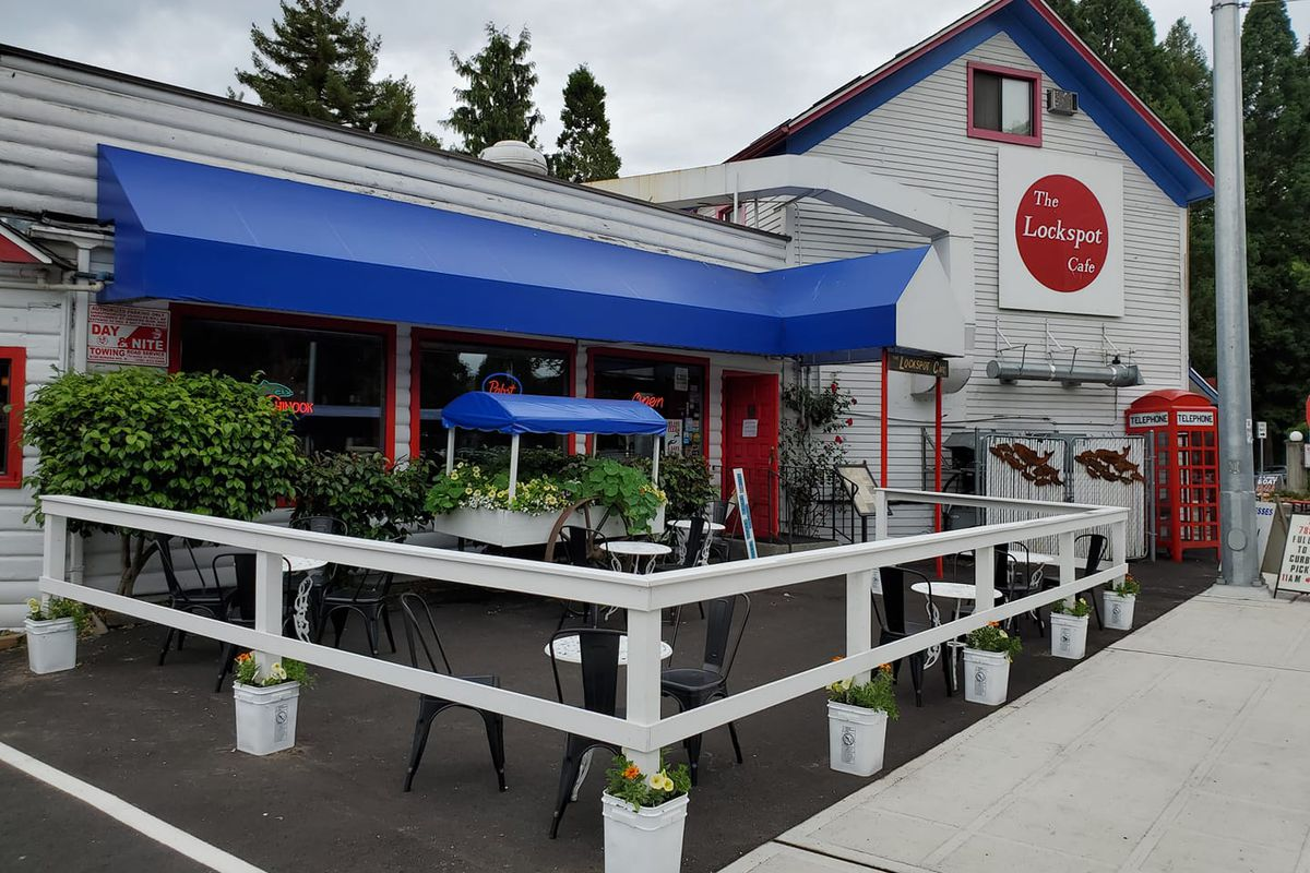 The exterior of the Lockspot Cafe in Ballard, with a blue awning and the restaurant's red sign out front