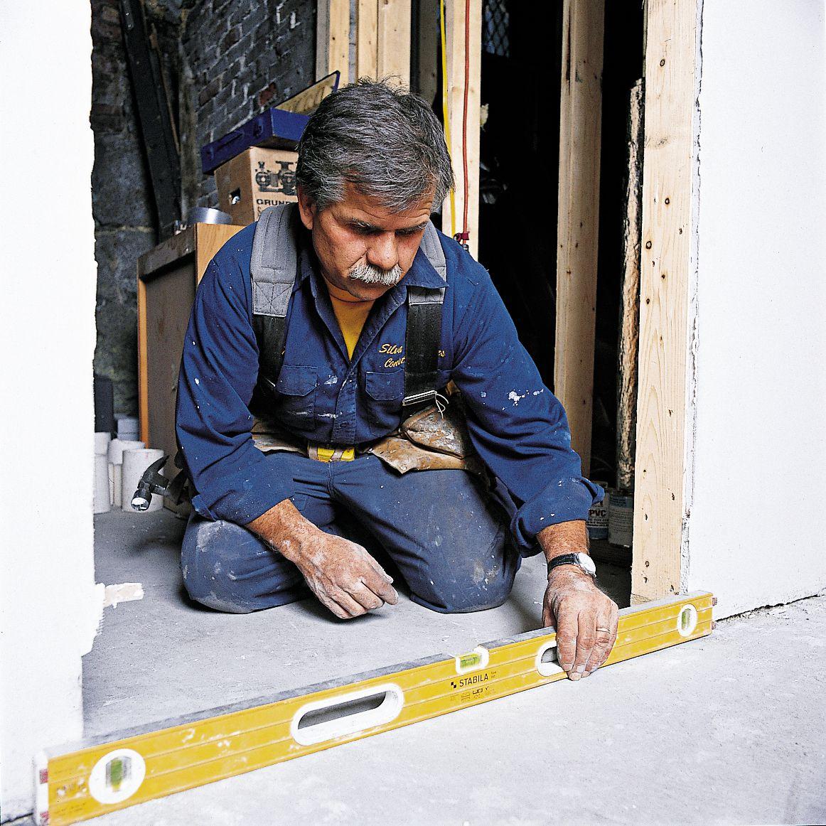 Man Using Level In Doorway To Install Prehung Interior Door
