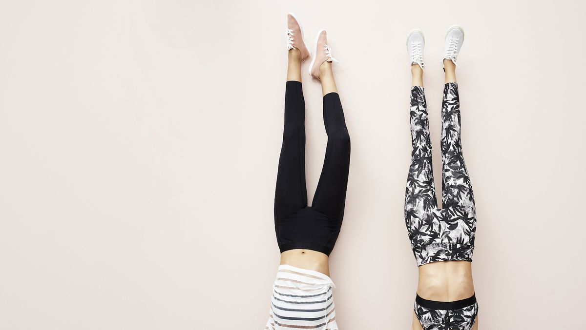 Two models wearing workout leggings with their legs in the air